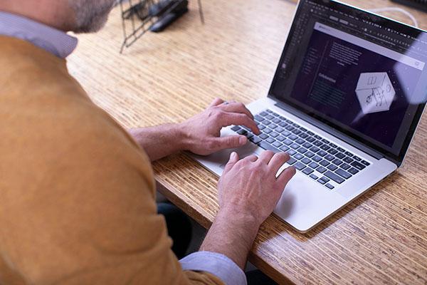 Man in mustard yellow sweater working on laptop.